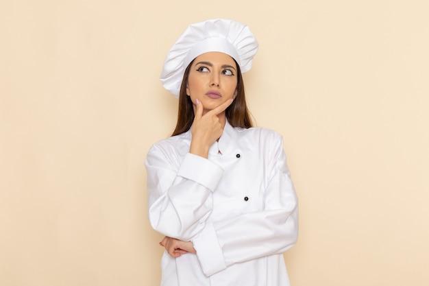 Vista frontal de uma jovem cozinheira em um terno de cozinheira branca, posando e pensando na parede branca