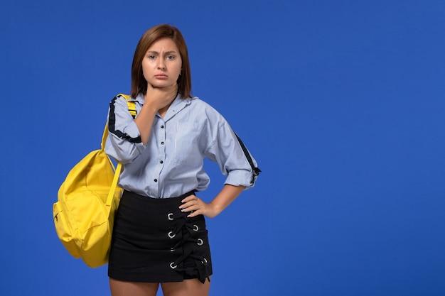 Vista frontal de uma jovem de camisa azul, com uma mochila amarela, pensando e tendo dor de garganta na parede azul