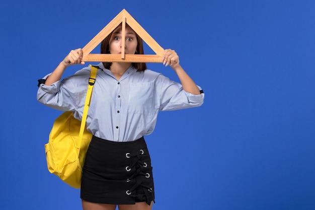 Vista frontal de uma jovem de camisa azul segurando a forma de um triângulo de madeira