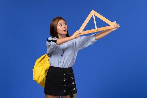 Vista frontal de uma jovem de camisa azul segurando um triângulo de madeira
