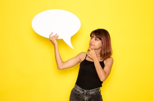 Vista frontal de uma jovem de camisa preta segurando uma grande placa branca pensando na parede amarelo-claro