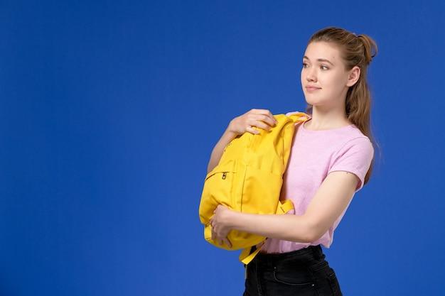 Vista frontal de uma jovem de camiseta rosa segurando uma mochila amarela na parede azul