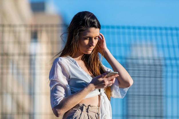 Vista frontal de uma jovem de pé ao ar livre enquanto estiver usando um telefone celular em um dia ensolarado