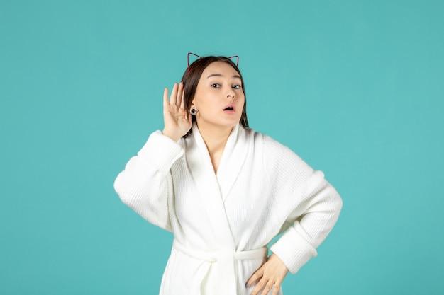 Vista frontal de uma jovem de roupão de banho na parede azul