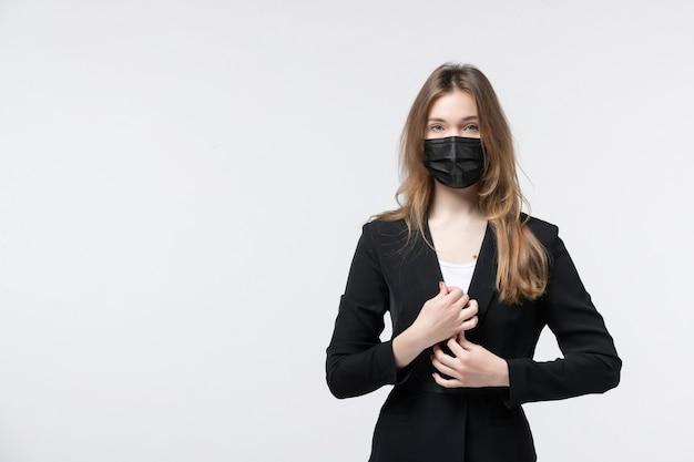 Vista frontal de uma jovem de terno usando máscara cirúrgica e posando para a câmera em branco