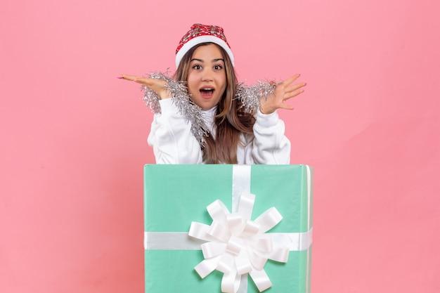 Vista frontal de uma jovem dentro do presente com guirlandas na parede rosa