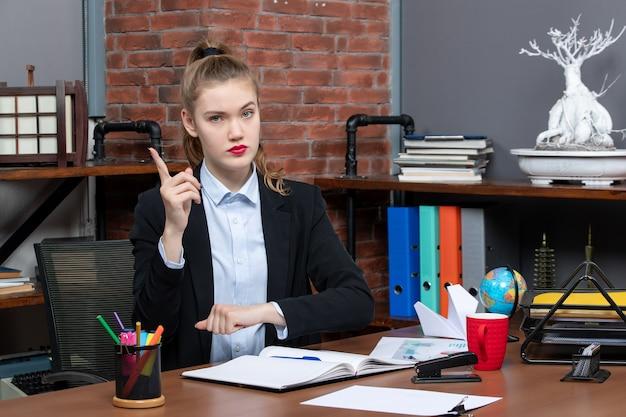 Vista frontal de uma jovem determinada sentada à mesa e apontando para cima no escritório