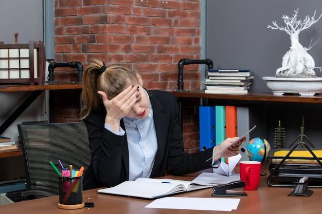 Vista frontal de uma jovem em pensamentos profundos, sentada à mesa e segurando um documento no escritório