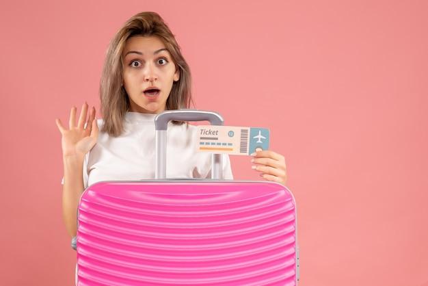 Vista frontal de uma jovem espantada com uma mala rosa segurando o ingresso