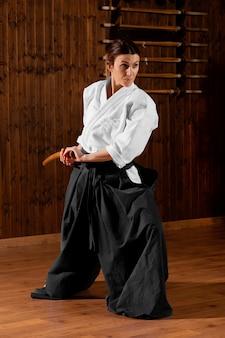 Vista frontal de uma jovem estagiária de artes marciais na sala de prática