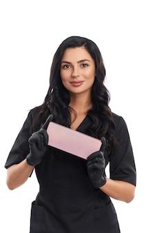 Vista frontal de uma jovem esteticista atraente em uniforme médico e luvas pretas segurando uma caixa de cosméticos rosa