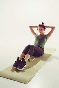 Vista frontal de uma jovem esticando o corpo na aula de ginástica.