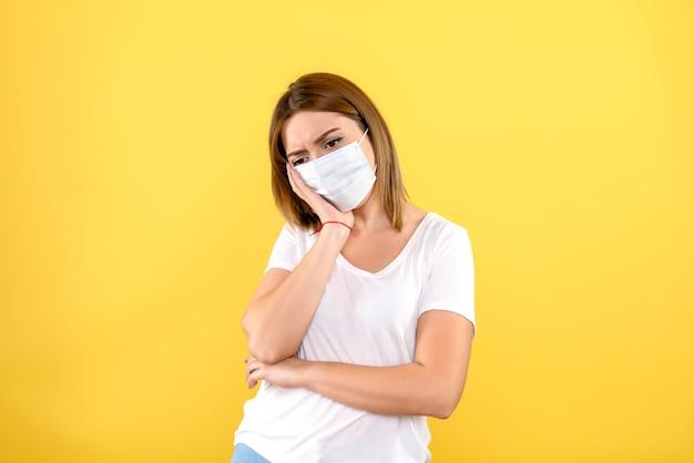 Vista frontal de uma jovem estressada na máscara na parede amarela