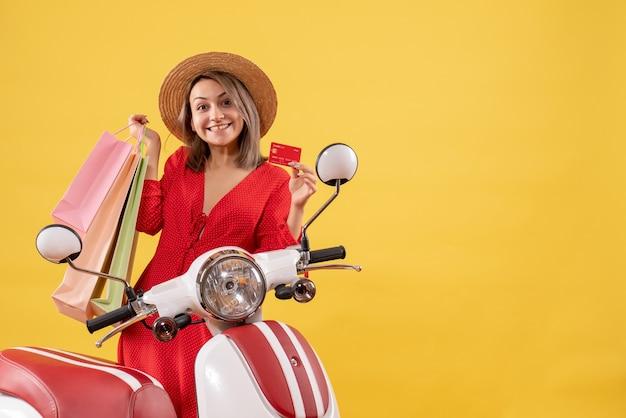 Vista frontal de uma jovem feliz com chapéu-panamá na motocicleta segurando sacolas de compras e um cartão