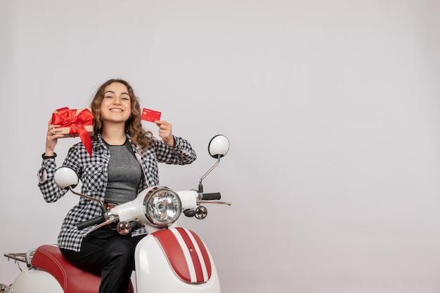 Vista frontal de uma jovem feliz em um ciclomotor segurando um cartão e um presente