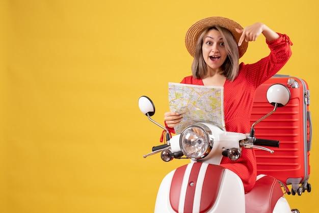Vista frontal de uma jovem feliz em uma motocicleta com uma mala vermelha segurando o mapa