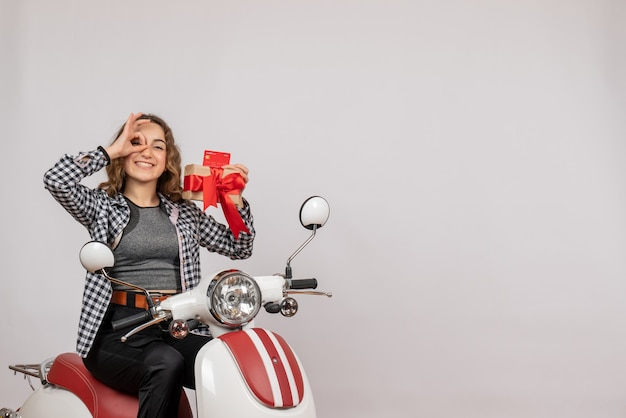 Vista frontal de uma jovem feliz em uma motocicleta segurando um presente fazendo binóculos na parede cinza