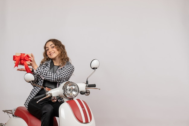 Vista frontal de uma jovem feliz em uma motocicleta segurando um presente na parede cinza