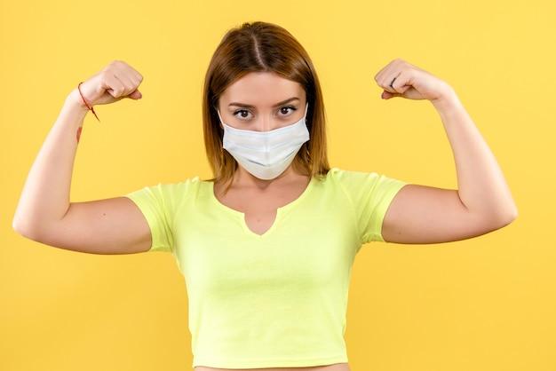 Vista frontal de uma jovem flexionando a máscara na parede amarela