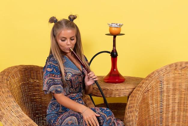 Vista frontal de uma jovem fumando narguilé na parede amarela
