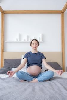 Vista frontal de uma jovem grávida sentada na cama em posição de lótus, praticando meditação