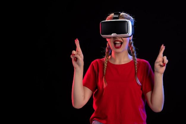 Vista frontal de uma jovem jogando fantasia de jogo escuro de realidade virtual