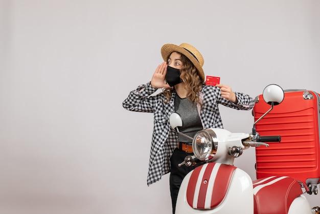 Vista frontal de uma jovem legal com máscara preta segurando o bilhete em pé perto da motocicleta vermelha