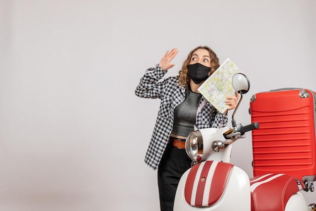 Vista frontal de uma jovem legal com máscara segurando um mapa em pé perto de motocicleta