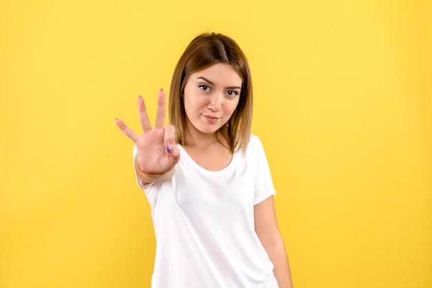 Vista frontal de uma jovem mostrando o número na parede amarela