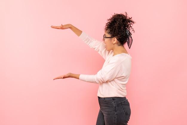 Vista frontal de uma jovem mostrando o tamanho na parede rosa claro