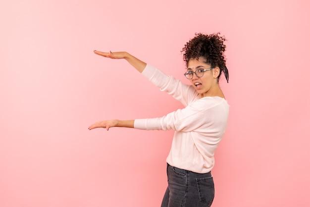 Vista frontal de uma jovem mostrando o tamanho na parede rosa