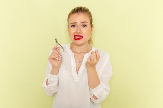 Vista frontal de uma jovem mulher atraente em uma camisa branca consertando as unhas na mesa verde