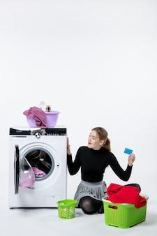 Vista frontal de uma jovem mulher com a máquina de lavar roupa segurando o cartão do banco na parede branca