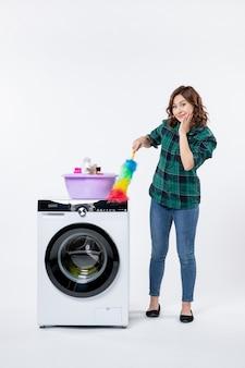 Vista frontal de uma jovem mulher com a máquina de lavar roupa segurando o limpador de pó na parede branca