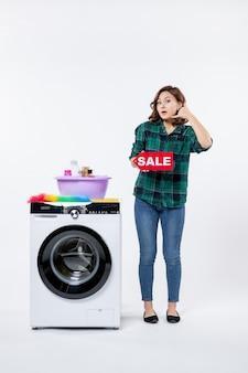 Vista frontal de uma jovem mulher com a máquina de lavar roupa segurando um banner de venda na parede branca