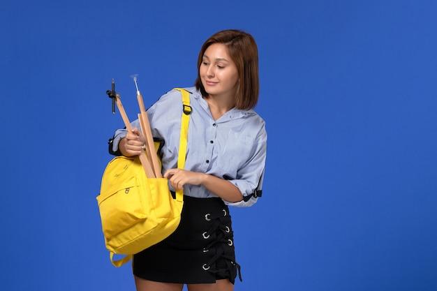 Vista frontal de uma jovem mulher com camisa azul, mochila amarela, segurando uma figura de madeira na parede azul clara