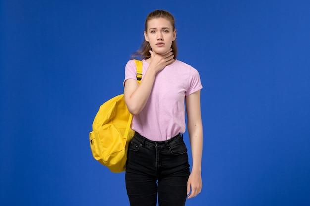 Vista frontal de uma jovem mulher com camiseta rosa e mochila amarela com dor de garganta na parede azul