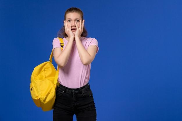 Vista frontal de uma jovem mulher com camiseta rosa e mochila amarela na parede azul