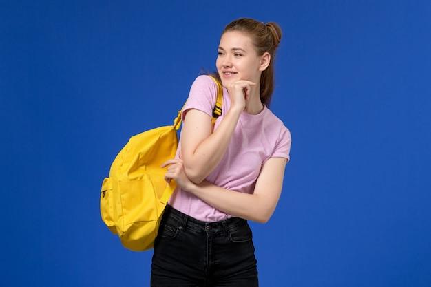 Vista frontal de uma jovem mulher com camiseta rosa e mochila amarela, posando na parede azul