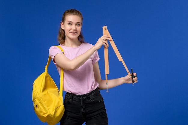 Vista frontal de uma jovem mulher com camiseta rosa e mochila amarela segurando uma figura de madeira sorrindo na parede azul