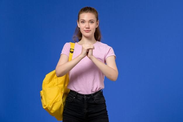 Vista frontal de uma jovem mulher com camiseta rosa e mochila amarela, sorrindo levemente na parede azul