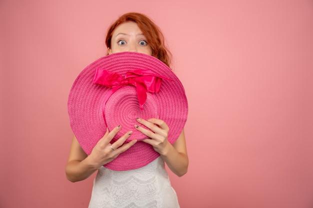 Vista frontal de uma jovem mulher com chapéu rosa na parede rosa
