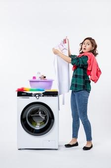 Vista frontal de uma jovem mulher com máquina de lavar, preparando roupas para lavar na parede branca