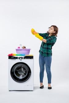 Vista frontal de uma jovem mulher com máquina de lavar roupa em luvas amarelas na parede branca
