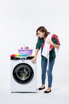 Vista frontal de uma jovem mulher com máquina de lavar roupa na parede branca