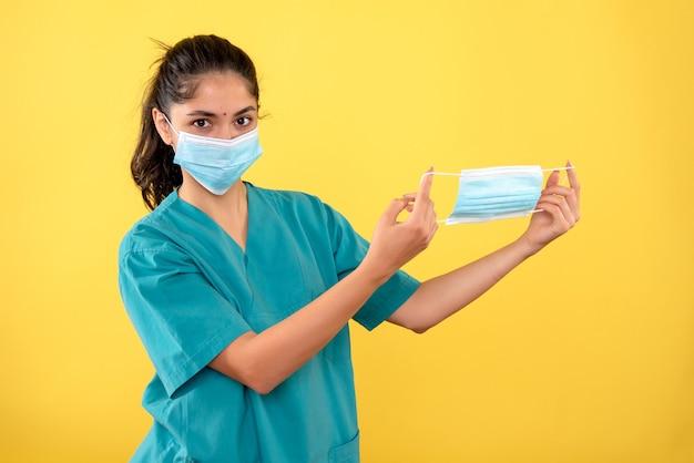 Vista frontal de uma jovem mulher com máscara médica segurando máscara na parede amarela