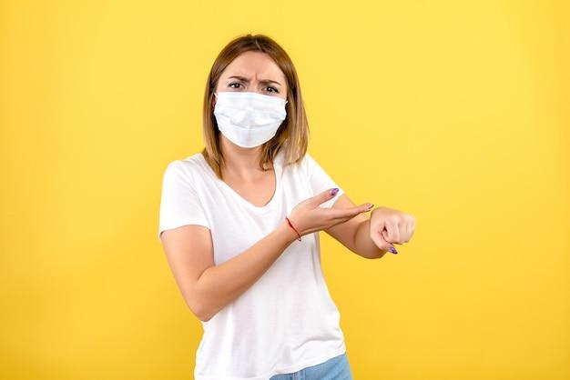 Vista frontal de uma jovem mulher com máscara na parede amarela