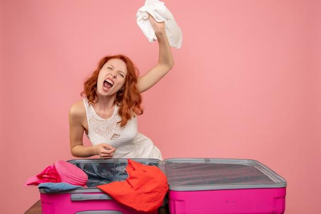 Vista frontal de uma jovem mulher com raiva jogando suas roupas na parede rosa