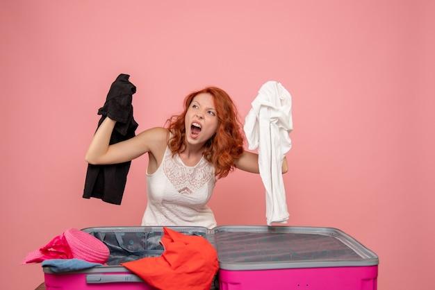 Vista frontal de uma jovem mulher com raiva preparando suas roupas para a viagem na parede rosa