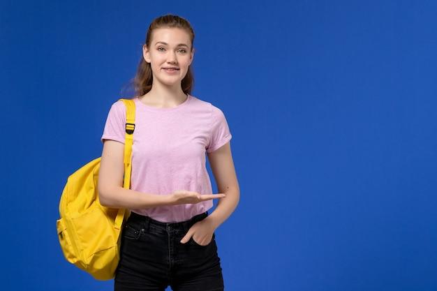 Vista frontal de uma jovem mulher com uma camiseta rosa e uma mochila amarela, sorrindo na parede azul clara